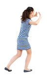 Back view of woman pushes wall. Isolated over white background. Rear view people collection. backside view of person. African-American woman in a striped dress Stock Photography