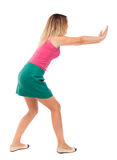 Back view of woman pushes wall. Stock Image