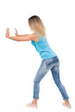 Back view of woman pushes wall. Isolated over white background. Rear view people collection. backside view of person. blonde in a blue shirt and jeans pushes Royalty Free Stock Images