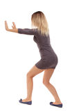 Back view of woman pushes wall Stock Photo