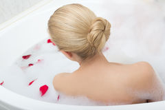 Back view of woman relaxing in bath with red flower petals Stock Photography