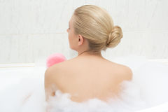 Back view of woman relaxing in bath and washing herself Stock Images