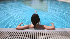 Back view of a woman relaxing in swimming pool stock video footage