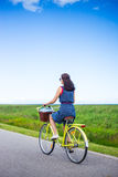 Back view of woman riding retro bicycle in countryside Stock Photo