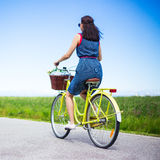 Back view of woman riding vintage bicycle with basket in country Stock Images
