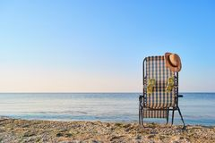 Back view woman`s hat on deck chair and attached flip flops. Concept of beach accessories stock images