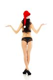 Back view woman with santa hat holding copyspace Royalty Free Stock Images