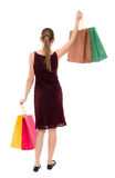 Back view of woman with shopping bags . beautiful brunette girl in motion.  backside   person. Royalty Free Stock Photos