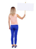 Back view woman showing sign board. Royalty Free Stock Image