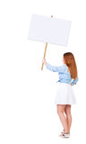 Back view  of woman showing a sign board. Stock Photos