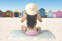 Back view of woman sits on beach. Summer Concept. Back view of young woman with long hair, sitting on the beach while wearing swimsuit and straw hat. Shot with Royalty Free Stock Photography