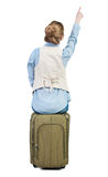 Back view of woman sits on a suitcase and pointing. Royalty Free Stock Photography