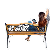 Back view of woman sitting on bench and looks at the screen  the tablet. Royalty Free Stock Images