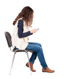 Back view of woman sitting on chair and looks at the screen of t Royalty Free Stock Images