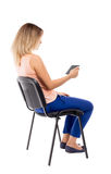 Back view of woman sitting on chair and looks at the screen of t Royalty Free Stock Photos