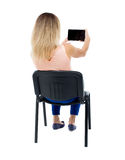 Back view of woman sitting on chair and looks at the screen of t Stock Image