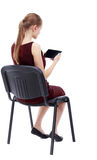 Back view of woman sitting on chair and looks at the screen Stock Photography