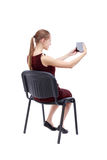 Back view of woman sitting on chair and looks at the screen Royalty Free Stock Photos