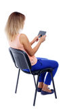 Back view of woman sitting on chair and looks at screen Stock Images