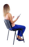 Back view of woman sitting on chair and looks at screen Royalty Free Stock Photos