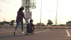 Back view of a woman sitting on a longboard while her friend is pushing her behind and running during sunset. Enjoying. Life. Lens flare. Slowmotion shot stock video