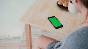 Back view of woman sitting at the table and drinking coffee in kitchen. Brunette girl uses smartphone, green screen. stock footage