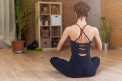 Bright young woman in brown jacket is standing stock photo for Living room yoga timetable