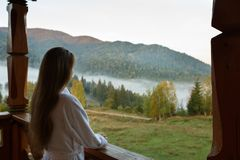 Back view of woman in spa bathrobe standing at wooden balcony of hotel resort room and enjoying beautiful morning alpain. Mountain and forest scenic royalty free stock photos