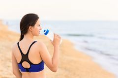 Woman drinks water on the sea beach royalty free stock image