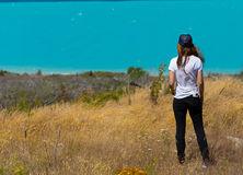 Back view of woman standing and looking out towards turquoise la Stock Image
