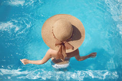 Back view of woman in straw hat relaxing in swimming pool on Tro. Pical Resort. Exotic Paradise. Travel, Tourism and Vacations Concept Stock Photography
