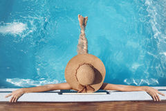 Back view of woman in straw hat relaxing in swimming pool on Tro. Pical Resort. Exotic Paradise. Travel, Tourism and Vacations Concept Royalty Free Stock Photography