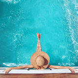 Back view of woman in straw hat relaxing in turquoise swimming p. Ool at luxury villa resort. Summer holiday idyllic background. Vacations Concept. Exotic Royalty Free Stock Photo