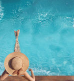 Back view of woman in straw hat relaxing in turquoise water swim. Ming pool at luxury villa resort. Summer holiday idyllic background. Vacations Concept. Exotic Royalty Free Stock Photo