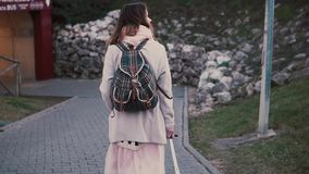 Back view of woman with suitcase and backpack walking in the city at evening. Girl moving to new place. Slow motion. Back view of woman with suitcase and stock footage