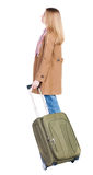 Back view of woman with suitcase looking up. Royalty Free Stock Image
