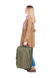 Back view of woman with suitcase looking up. Royalty Free Stock Photo