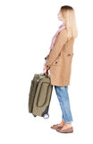 Back view of woman with suitcase looking up. Royalty Free Stock Images