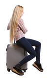 Back view of woman with suitcase looking up. Standing young girl. Stock Photo