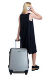 Back view of woman with suitcase looking up. Stock Photography
