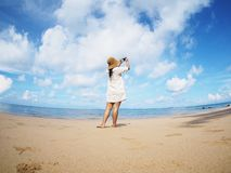 Back view woman taking photograph on the beach., fish eye lens distortion. Back view woman taking photograph on the beach. Happy people on summer holiday royalty free stock images