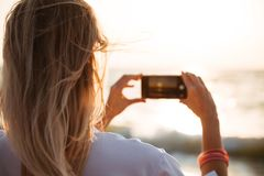 Back view of a woman taking a picture of a sunset. At the beach with mobile phone Stock Photography