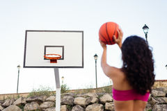Back view of woman throwing basket ball outside Stock Photography