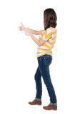 Back view of  woman thumbs up. Rear view people collection. backside view of person. Isolated over white background. slender brunette in a jeans shows the Royalty Free Stock Photography