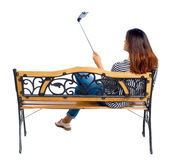Back view of a woman to make  selfie stick portrait sitting on the bench. Stock Photos