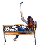 Back view of a woman to make  selfie stick portrait sitting on the bench. Stock Image