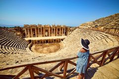 Back view of woman traveler in hat looking at amazing Amphitheater ruins in ancient Hierapolis, Pamukkale, Turkey. Grand panorama stock photos