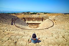 Back view of woman traveler in hat looking at amazing Amphitheater ruins in ancient Hierapolis, Pamukkale, Turkey. Grand panorama. Back view of woman traveler in royalty free stock photo