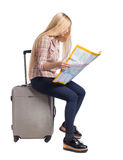 Back view of woman traveler sitting on their suitcases and looking for a route map. Backside view of person.  Rear view people collection. Isolated over white Royalty Free Stock Photography