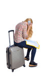 Back view of woman traveler sitting on their suitcases and looking for a route map, talking  the phone. Back view of woman traveler sitting on their suitcases Royalty Free Stock Photos